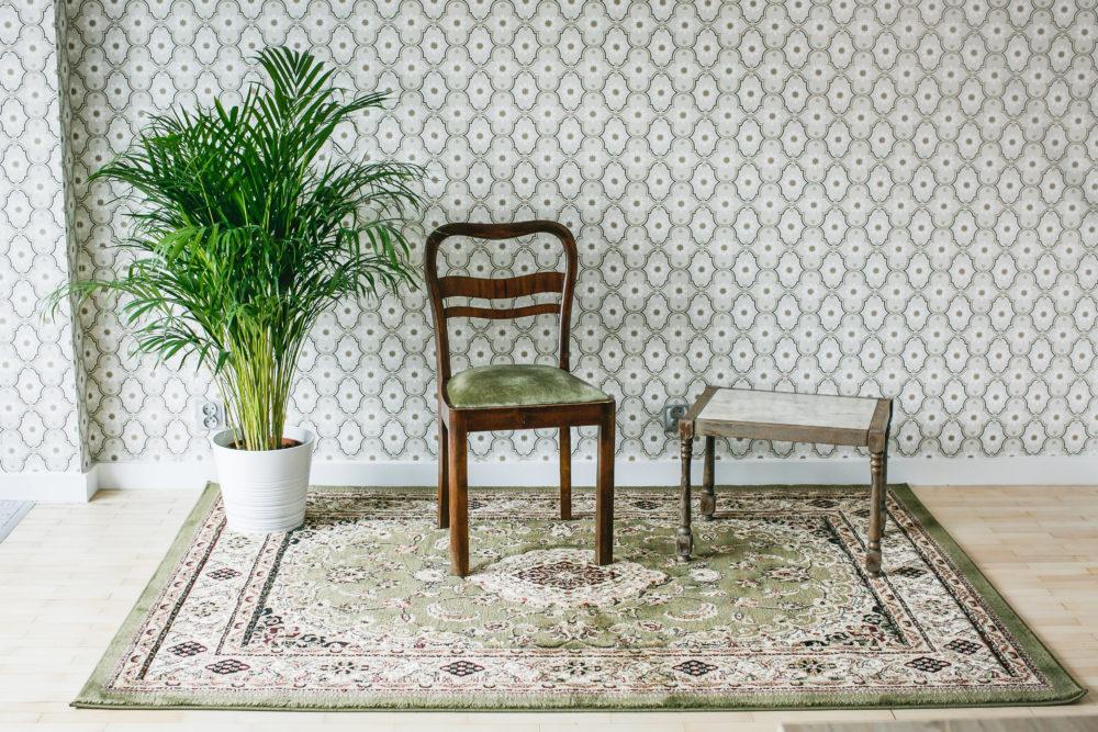 krzesło, ściana i dywan w klimacie PRL