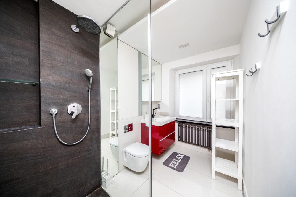 plan zdjęciowo filmowy łazienka z przezroczystą szkjlaną kabiną prysznicową i stylowym czerwonym wykończeniem